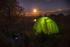 Night landscape with a tent and a full moon near the Nerl River, Russia Royalty Free Stock Image