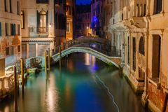 Night lateral canal and bridge in Venice, Italy. Lateral canal and pedestrian bridge in Venice at night with street light illuminating bridge and houses, Italy Royalty Free Stock Photos