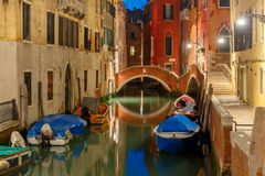 Night lateral canal and bridge in Venice, Italy. Lateral canal and pedestrian bridge in Venice at night with street light illuminating bridge and houses, with stock image