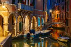 Night lateral canal and bridge in Venice, Italy. Lateral canal and pedestrian bridge in Venice at night with street light illuminating bridge and houses, with Royalty Free Stock Photography