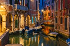 Night lateral canal and bridge in Venice, Italy. Lateral canal and pedestrian bridge in Venice at night with street light illuminating bridge and houses, with Stock Images