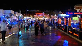 Night life in Naama Bay Street, Egypt, Sharm el Sheikh. EGYPT, SHARM EL SHEIKH, APRIL 8, 2019: Night life in Naama Bay Street. Tourists walk near the stalls with stock video footage