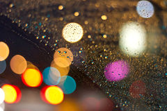 Night Life. Rain on glass at night with the city lights in the background stock photos