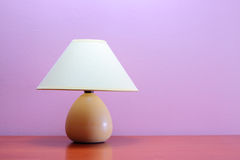 Night light. Lamp on a wooden table against purple wall Stock Photos
