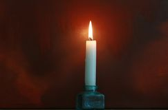 Night Light. A single candle set in a glass pot against a dark grunge style background.  Evocative mood, copy space available Royalty Free Stock Photography