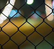 Night light bokeh road behind grate Stock Images