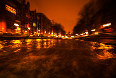 Night lighting reflections in Amsterdam channels from moving cruise boat. Blurred abstract photo as background. Royalty Free Stock Image