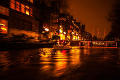 Night lighting reflections in Amsterdam channels from moving cruise boat. Blurred abstract photo as background. Royalty Free Stock Images