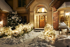 Night lights. Outside Christmas lights line path to a front door on a snowy evening Royalty Free Stock Image