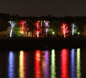 Night lights. Night view of coloured trees reflected in a river Royalty Free Stock Photo