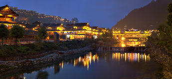 Night lights of big Chinese village, reflected in river water. Royalty Free Stock Photo