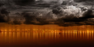 Night lights from modern city reflecting on water. City lights from the Melbourne Causeway lighting up the night sky and Indian River Lagoon royalty free stock photos