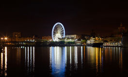 Night lights in the port of Malaga. Ferris wheel in the background. Stock Photo