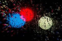 Night lights and rain. Photo night street through wet glass stock images