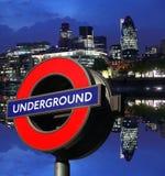 Night London cityscape with Underground symbol. LONDON -May 20: Modern London May 20, 2011 in London. The London 'Underground' logo used  for transportation Royalty Free Stock Images