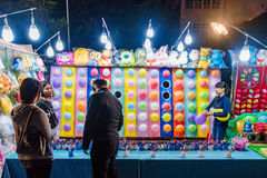 Night market dart game in Shilin. TAIPEI, TAIWAN - MAY 20: This is a game in Shilin night market where people can win soft toys by hitting balloons with darts it stock images