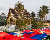 Night Market under the Wat Xieng Thong, Luang Prabang. Wide view of red and blue tents of a night marker under the temple of Xieng Thong in Luang Prabang, Laos Royalty Free Stock Photography