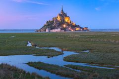 Night Mont Saint Michel, Normandy, France. Famous Mont Saint Michel Illuminated in the evening blue hour with reflection in the canal on the water meadows royalty free stock images
