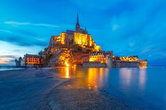 Night Mont Saint Michel, Normandy, France. Famous Mont Saint Michel Illuminated in the evening blue hour with reflection at high tide, Normandy, France Royalty Free Stock Image