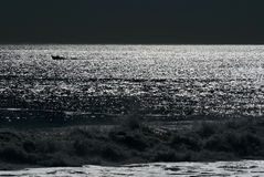 Night moon over ocean. With boat silhouette royalty free stock photography