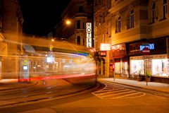 Night motion blur of fast moving tram on a street. Night motion blur of fast moving tram on the street of austrian capital in Vienna. The Wiener Linien vehicle Royalty Free Stock Photo