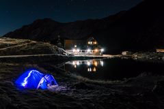 Night mountain landscape with illuminated blue tent. Mountain peaks and the moon. outdoor at Lacul Balea Lake, Transfagarasan,. Romania. Concept Travel stock photography