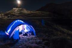 Night mountain landscape with illuminated blue tent. Mountain peaks and the moon. outdoor at Lacul Balea Lake, Transfagarasan,. Romania. Concept Travel, copy stock photography