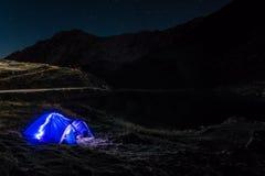 Night mountain landscape with illuminated blue tent. Mountain peaks and the moon. outdoor at Lacul Balea Lake, Transfagarasan,. Romania. Concept Travel, copy stock photo