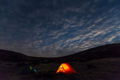 Night mountain landscape with illuminated tent. Silhouettes of mountain Ridge night sky with many stars Clouds highlighted by last Sunbeams on background Stock Image
