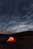 Night mountain landscape with illuminated tent. Silhouettes of mountain Ridge night sky with many stars Clouds highlighted by last Sunbeams on background Royalty Free Stock Photos