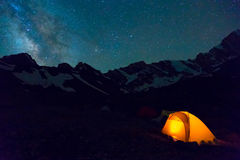 Night mountain landscape with illuminated tent. Silhouettes of snowy mountain peaks and edges night sky with many stars and milky way on background illuminated Stock Photo