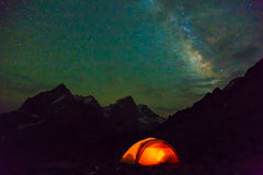 Night mountain landscape with illuminated tent. Silhouettes of snowy mountain peaks and edges night sky with many stars and milky way on background illuminated Stock Photography