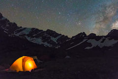 Night mountain landscape with illuminated tent. Silhouettes of snowy mountain peaks and edges night sky with many stars and milky way on background illuminated Stock Image