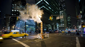 Night in New York. Image of night street in New York with speeding taxi and steam pipe stock image