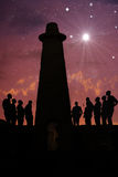 Night at the old lighthouse. People singing  at the lighthouse at sunset Royalty Free Stock Photo
