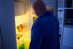 At night overweight guy open refrigerator Stock Image