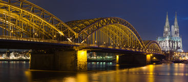 Night panoram of Cologne. Cathedral and railway bridge over river Rhine royalty free stock image