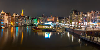 Night panorama of Amsterdam canal Damrak, Holland. Beautiful typical Dutch dancing houses, Oude Kerk church and tourist boats at the Amsterdam canal Damrak at Stock Image