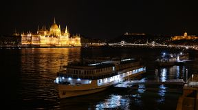 Night panorama of Budapest. City centre with Parliament building, Chain Bridge, Buda Castle, Danube river and two boats Stock Image