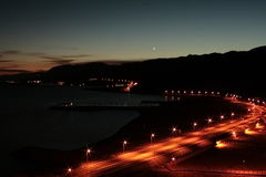 Night panorama on light curve road. Near night red sea line and outline of black mountains on the sunset sky background Stock Photo