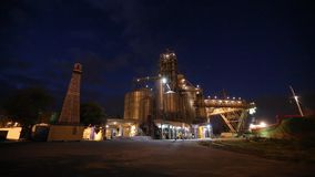 Night panorama of loading grain crops on bulk freighter ship via trunk to open cargo holds at silo terminal in seaport. From above. Cereals bulk transshipment stock video