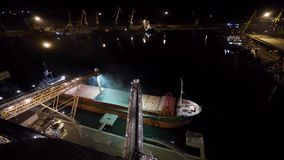 Night panorama of loading grain crops on bulk freighter ship via trunk to open cargo holds at silo terminal in seaport. From above. Cereals bulk transshipment stock footage
