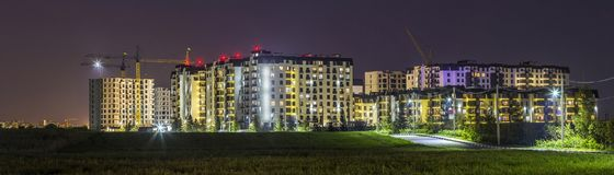 Night panorama of new built and still under construction apartment buildings stock photo