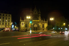 Night in Paris. Urban scene in Paris, an old church can be seen in the background. Trail lights in the foreground stock photos