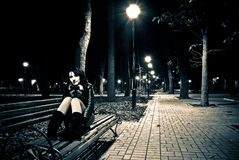 Night park view. Young woman sitting on a bench at the night park alley stock photography