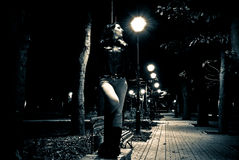 Night park view. Young woman standing under streetlight at the night park alley Stock Photos