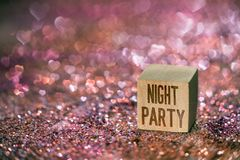 Night party text with heart bokeh light. Night party text written on wooden cube on color glitter with beautiful real heart shape bokeh light stock photography