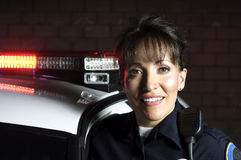 Night patrol. A Hispanic female officer standing in the night with her patrol car royalty free stock photos