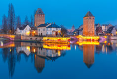Night Petite France in Strasbourg, Alsace. Medieval towers and bridges Ponts Couverts with mirror reflections in Petite France during twilight blue hour Royalty Free Stock Photography