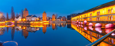 Night Petite France in Strasbourg, Alsace. Panorama of medieval towers, bridges Ponts Couverts and Barrage Vauban with mirror reflections in Petite France during Stock Photo